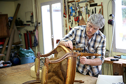 Craftsman repairing antique armchair in workshop